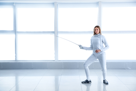 Young female fencer training in gym