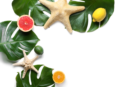 Summer composition with fresh monstera leaves, fruits and starfish on white background