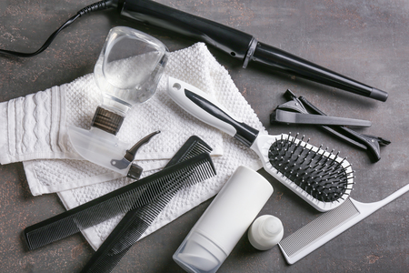 Professional hairdresser's set with cosmetics on grey table