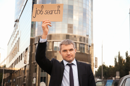Businessman holding piece of cardboard with text JOB SEARCH outdoors