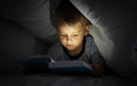 Cute little boy reading book in bed under blanket Imagens - 117935606