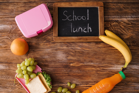 Composition with appetizing food and small chalkboard with words SCHOOL LUNCH on wooden background