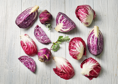 Different types of cabbage on light wooden background