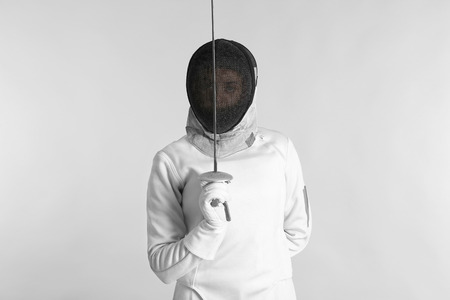 Young female fencer on light background