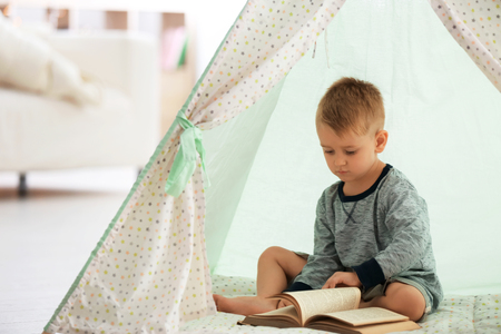 Cute little boy reading book in hovel at home Imagens - 117937500