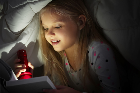 Cute little girl with flashlight reading book in bed under blanket Imagens - 117938903
