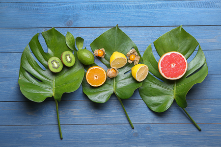 Various delicious exotic fruits with tropical leaves on color wooden background