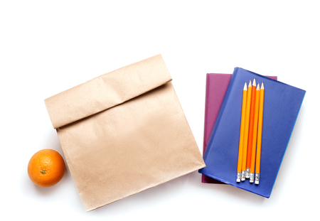 Lunch bag with orange and stationery on white background