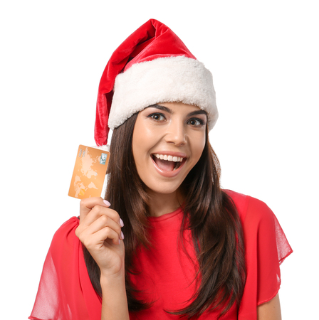 Young woman in Santa hat with credit card on white background. Online shopping