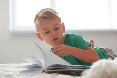 Cute little boy reading book on bed at home Imagens - 117990984