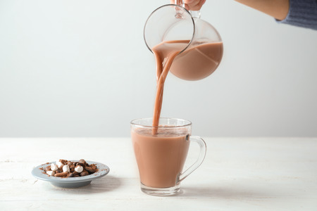 Woman pouring tasty cocoa from jug into cup on white table