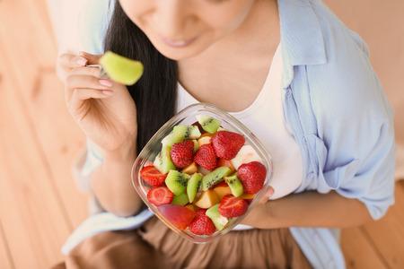 Mujer comiendo ensalada de frutas saludables en casa, primer plano Foto de archivo