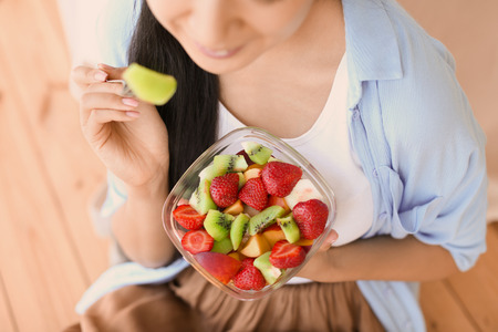 Woman eating healthy fruit salad at home, closeup
