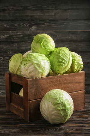 Crate with fresh cabbages on wooden table