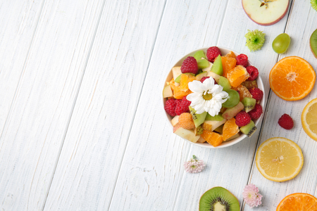 Bowl with delicious salad and sliced fruits on light wooden table