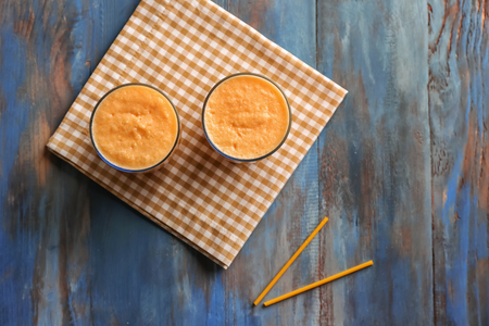 Glasses of tasty melon smoothie on wooden table