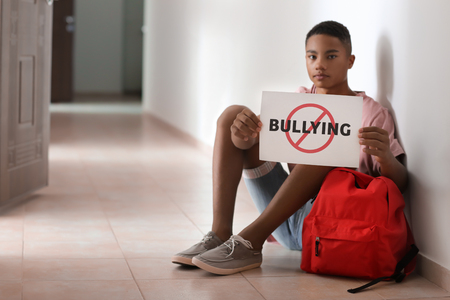 African-American teenage boy holding sheet of paper with word BULLYING while sitting on floor at school