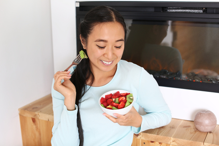 Asian woman eating healthy fruit salad at home 写真素材