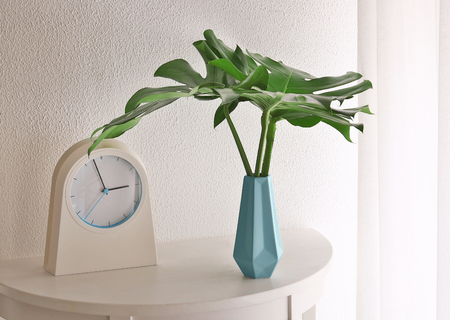 Tropical leaves in vase with clock on table near light wall indoors Archivio Fotografico