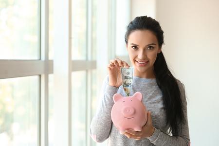 Mujer joven poniendo dinero en la hucha cerca de la ventana