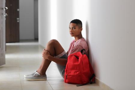 Sad African-American teenage boy sitting on floor indoors. Bullying at school