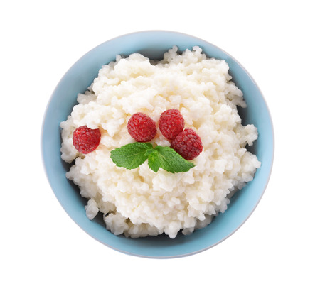 Delicious rice pudding with raspberry in bowl on white background