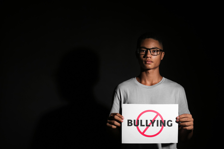 African-American teenage boy holding sheet of paper with word STOP on dark background
