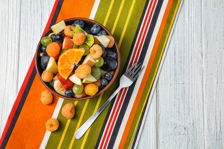 Delicious fruit salad in bowl on colorful napkin Фото со стока