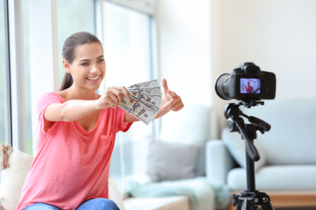 Young female blogger with money recording video indoors Imagens