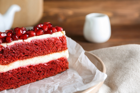 Piece of delicious pomegranate cake on plate, closeup