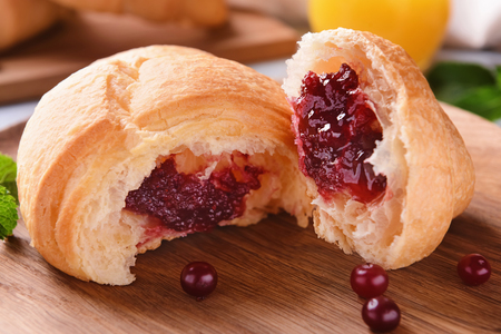Tasty croissant with berry jam on wooden board, closeup 免版税图像