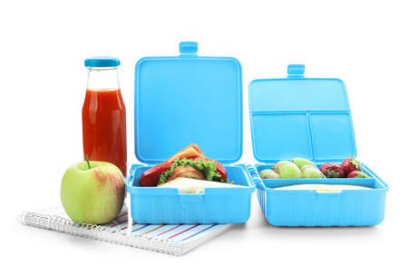 Lunch boxes with appetizing food and notebook on white background