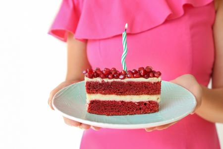 Woman holding piece of delicious birthday cake with burning candle on light background Stock Photo