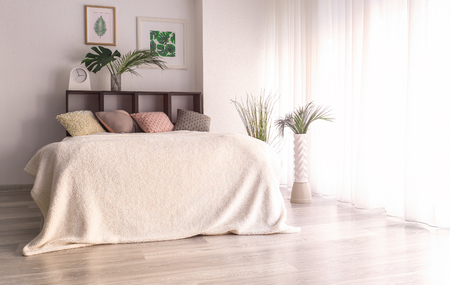 Interior of modern comfortable bedroom with tropical leaves