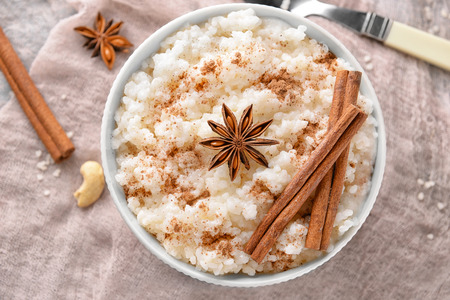 Bowl with tasty rice pudding, cinnamon and anise on gauze cloth