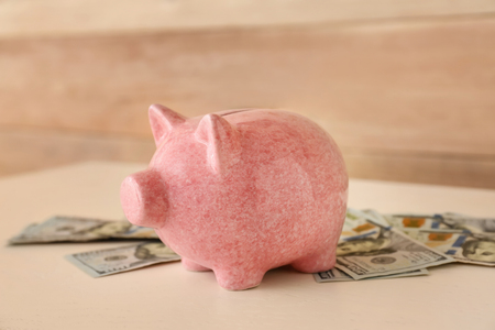 Piggy bank with money on light table Banque d'images