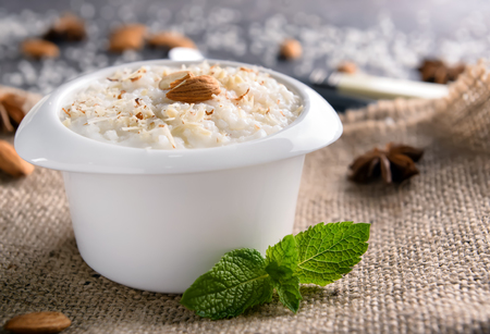 Bowl with delicious rice pudding and almond nuts on sackcloth