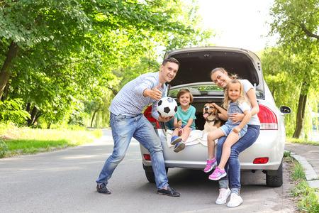 Gelukkig gezin met schattige hond in de buurt van auto buitenshuis