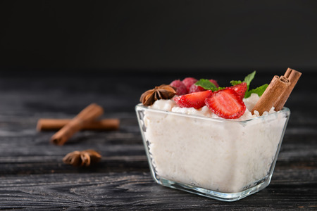 Glass bowl with delicious rice pudding and berries on black wooden table Stock Photo