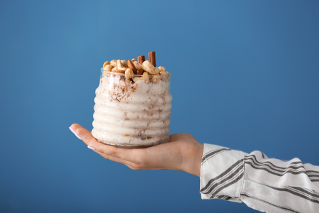Woman holding jar with delicious rice pudding on color background Standard-Bild - 115051036