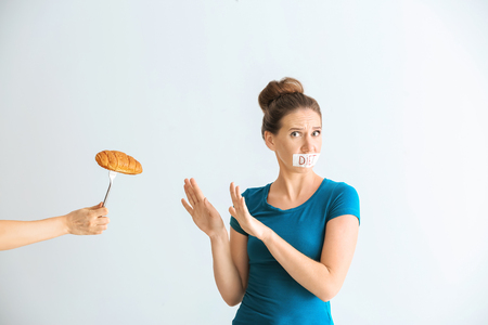 Woman with taped mouth refusing to eat unhealthy food on white background. Diet concept