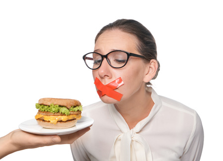 Offering of tasty burger to woman with taped mouth on white background. Diet concept Stock Photo
