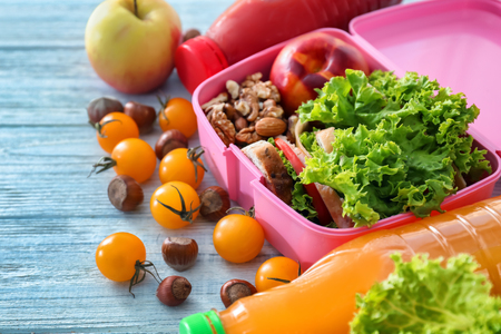 Lunch box with appetizing food and bottles of juice on light wooden table Stock Photo