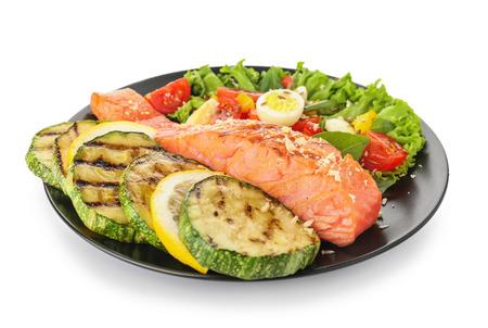Bord met smakelijke zalm en verse salade op witte achtergrond