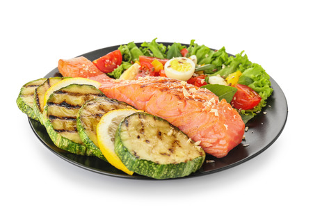 Plate with tasty salmon and fresh salad on white background