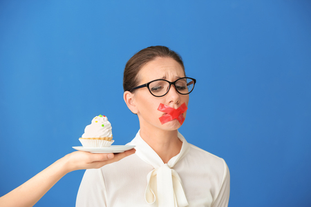 Offering of tasty tartlet to woman with taped mouth on color background. Diet concept 免版税图像