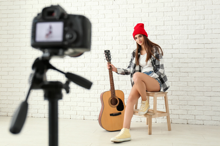 Young female musician recording video indoors 版權商用圖片