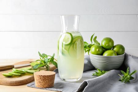 Jug of fresh lime lemonade on table