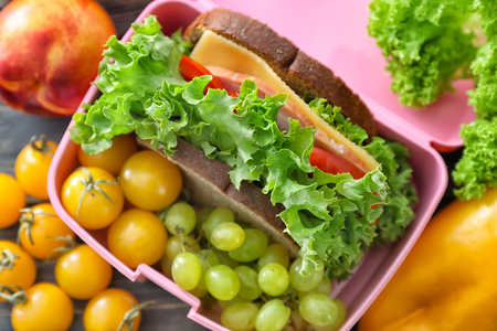 Lunch box with appetizing food on table