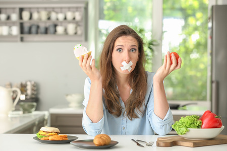 Stressful woman with taped mouth and different products in kitchen. Choice between healthy and unhealthy food